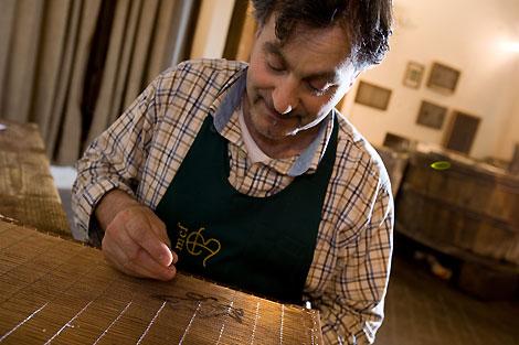 Il mastro cartaio cuce la filigrana di metallo sopra le vergelle della forma